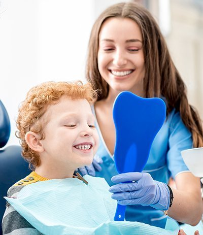 child with dentist looking into mirror